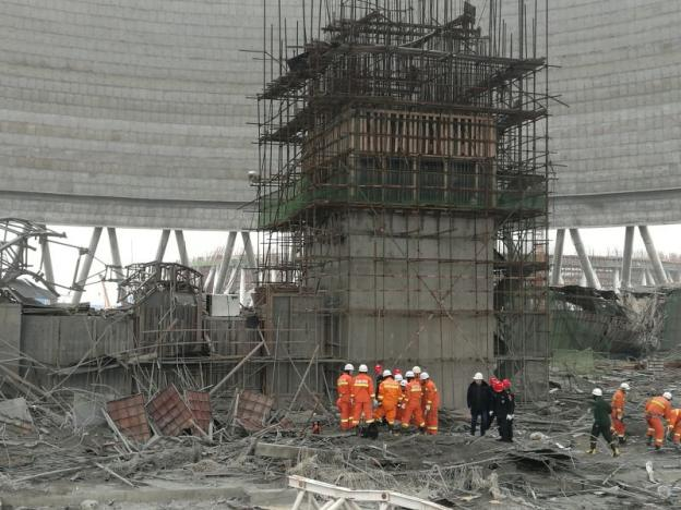 Rescue workers search the site where a power plant's cooling tower under construction collapsed, in Fengcheng
