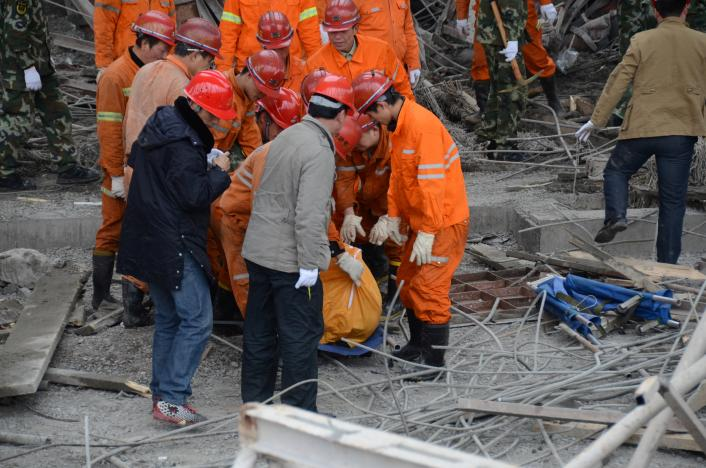 Rescue workers carry out a victim at the site where a power plant's cooling tower under construction collapsed in Fengcheng, Jiangxi province, China.
