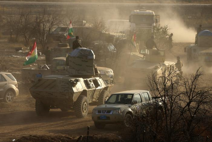 Military vehicles of Peshmerga forces drive in the town of Bashiqa, east of Mosul, during an operation to attack Islamic State militants in Mosul, Iraq.