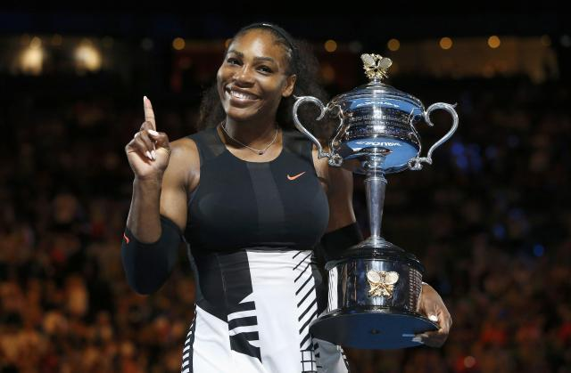 Serena Williams of the U.S. gestures while holding her trophy after winning her Women's singles final match against Venus Williams of the U.S.