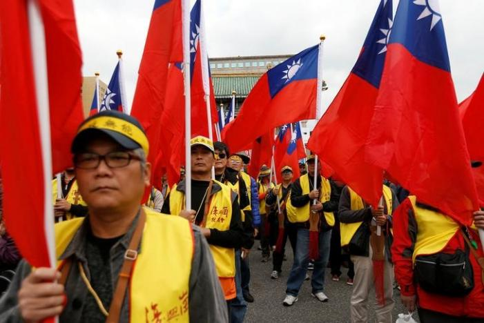 Protesters hold Taiwanese national flags as they take part in a rally against the overhaul of the military and civil service pension fund, outside the Presidential Office in Taipei,Taiwan.