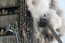 Firefighters try to put out a fire in a blazing high-rise building in Tehran, Iran.