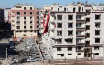 Damaged cars and buildings are seen after Friday's explosion outside a housing complex in the southeastern Turkish town of Viransehir in Sanliurfa province, Turkey, near the border with Syria.