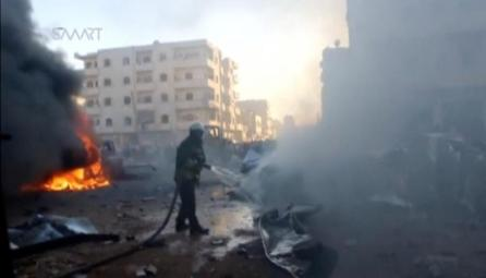 A still image taken from a video posted to a social media website on June 24, 2017, shows a civil defence member trying to put out a fire at the site of a car bomb, said to be in the town of al-Dana, in Syria's rebel-held Idlib province.