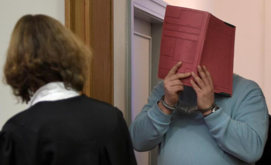 FILE PHOTO: Former nurse Niels H. masks his face with a folder on his arrival in the courtroom in Oldenburg