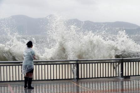 A woman stands beside a big wave on a waterfront Typhoon Hato hitting in Hong Kong, China.