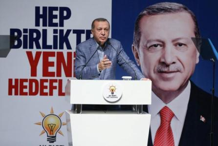 """Turkish President Tayyip Erdogan speaks during a meeting of his ruling AK Party in Rize, Turkey. The party banner in the background reads that: """"Together with new targets""""."""