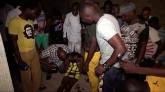 A wounded restaurant customer sits on the ground following an attack by gunmen on a restaurant in Ouagadougou, Burkina Faso.