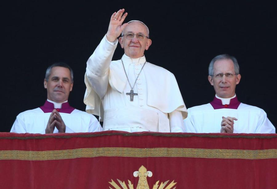 "Pope Francis waves as he leads the ""Urbi et Orbi"" (to the city and the world) message from the balcony overlooking St. Peter's Square at the Vatican"