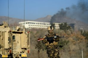 An Afghan security personnel keeps watch near the site of an attack on the Intercontinental Hotel in Kabul, Afghanistan.
