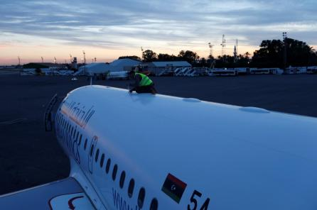 A man fixes a plane damaged during clashes at Mitiga airport in Tripoli, Libya.