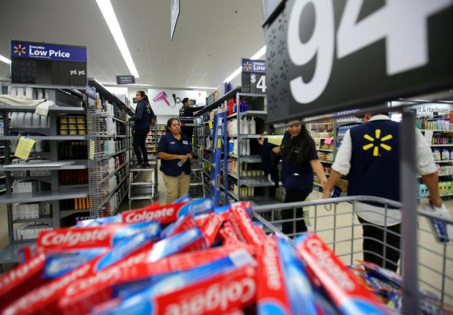Workers prepare their store for customers at a newly built Walmart Super Center in Compton.