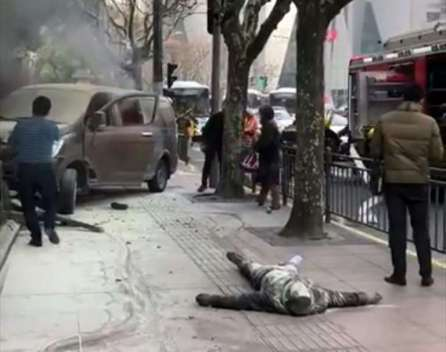 An injured person lies on the ground after a van caught fire and ploughed into pedestrians in Shanghai, China.