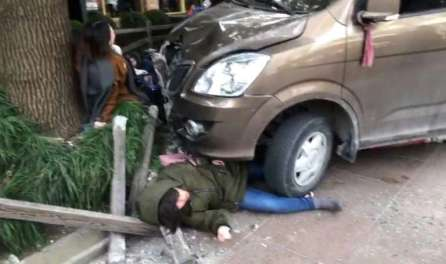 An injured person lies trapped between a van and a fence after the vehicle caught fire and hit pedestrians in Shanghai, China.