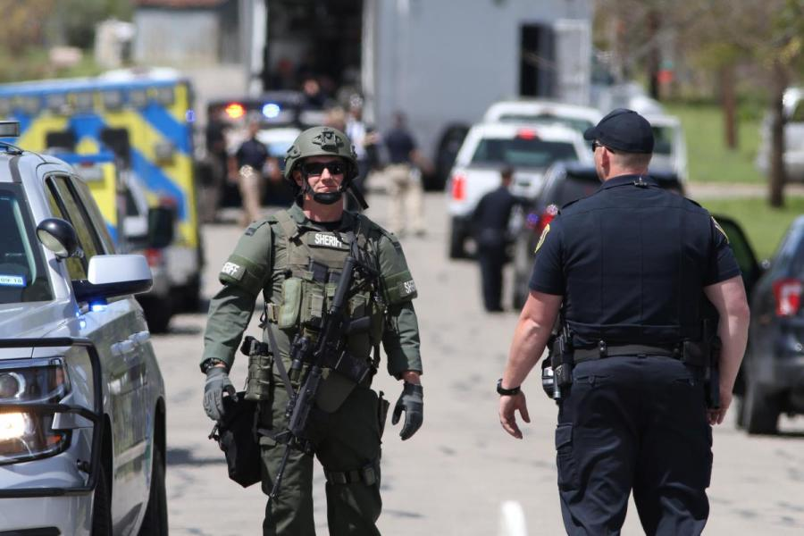 Law enforcement personnel investigate a neighborhood containing the home where the bomber was suspected to have lived in Pflugerville