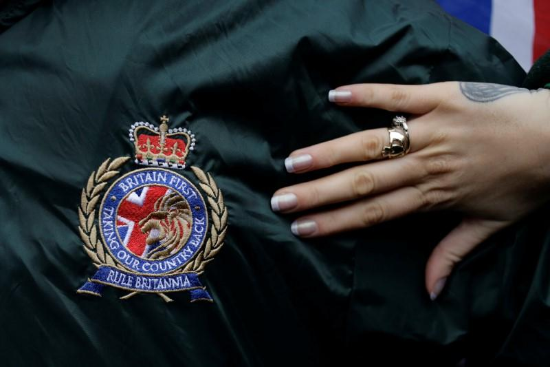A woman's hand and the logo of Britain First during a rally in Rochester