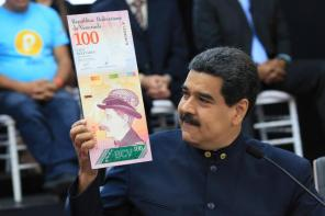 Venezuela's President Nicolas Maduro holds a sample of the new hundred bolivars note during a meeting with the ministers responsible for the economic sector at Miraflores Palace in Caracas, Venezuela.