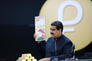 Venezuela's President Nicolas Maduro holds a specimen of the new one hundred-bolivar banknote during a meeting with ministers responsible for the economic sector at Miraflores Palace in Caracas, Venezuela.