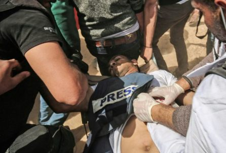 Palestinians attend to wounded Palestinian journalist Yasser Murtaja during clashes with Israeli troops at the Israel-Gaza border, in the southern Gaza Strip.