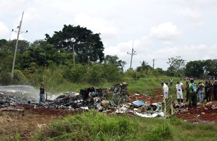 Rescue team members work in the wreckage of a Boeing 737 plane that crashed in the agricultural area of Boyeros, around 20 km (12 miles) south of Havana, shortly after taking off from Havana's main airport in Cuba.