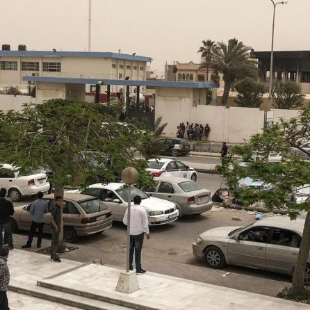 People gather outside the electoral commission headquarters following suicide attacks in Tripoli, Libya.