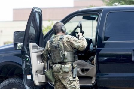 An FBI agent is seen checking an SUV at Santa Fe High School following a shooting incident in Santa Fe, Texas, U.S.