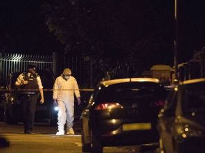Police and forensic investigators are seen at the house of former Sinn Fein leader Gerry Adams following an explosive attack in western Belfast, Northern Ireland.