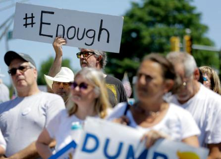 A man holds a sign that reads 'Enough' during a rally against the Trump administration immigration policies in Bedminster, New Jersey, U.S.