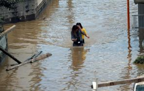 Women make their way through a flooded area in Mabi town in Kurashiki, Okayama Prefecture, Japan.