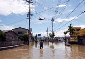 A man makes his way in a flooded area in Mabi town in Kurashiki, Okayama Prefecture, Japan.