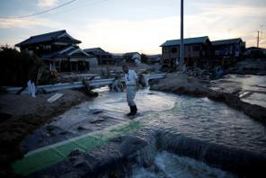 A local resident walks in a flooded area in Mabi town in Kurashiki, Okayama Prefecture, Japan.