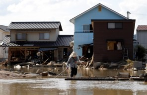 An elderly woman walks next to submerged and destroyed houses in a flooded area in Mabi town in Kurashiki, Okayama Prefecture, Japan.