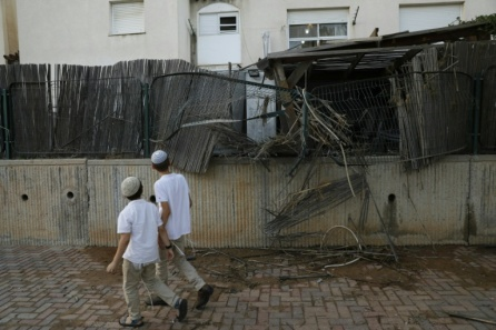 Boys walk past a fence in the Israeli town of Sderot damaged by an earlier round of rocket fire from Gaza.