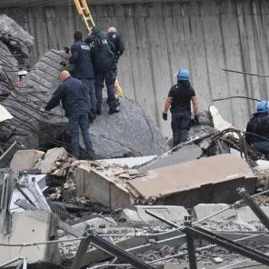 Rescue workers are seen climbing over the rubble of a collapsed portion of the Morandi Bridge in Genoa, Italy.