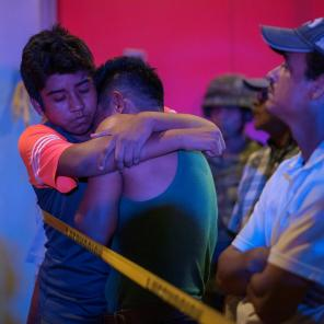 A man is comforted at a crime scene following a deadly attack at a bar by unknown assailants in Coatzacoalcos, Mexico.