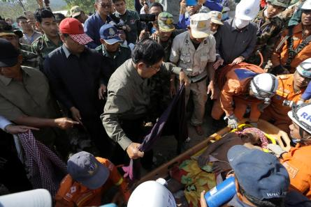 Cambodia's Prime Minister Hun Sen covers a victim from the collapsed building which was under construction in Kep, Cambodia.