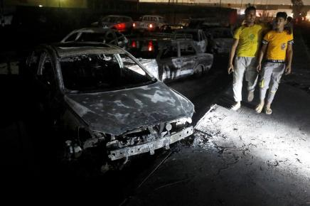 People walk past burned vehicles following a fire that broke out in Egypt\u0027s Shuqair-Mostorod crude oil pipeline, at the beginning of Cairo-Ismailia road, Egypt.