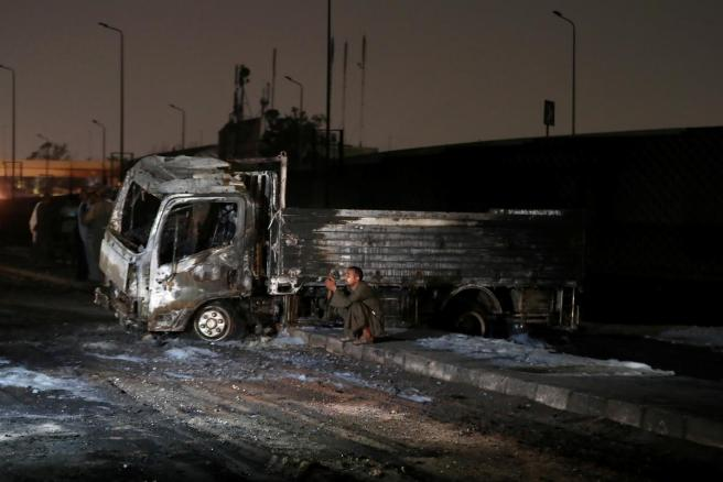 A man sits next to a burned truck following a fire that broke out in?Egypt\u0027s Shuqair-Mostorod crude oil?pipeline, at the beginning of Cairo-Ismailia road, Egypt.